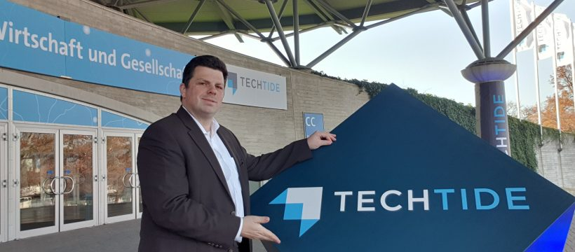 Christoph Rothe zeigt das TechTide-Schild am Eingang des Convention Centers